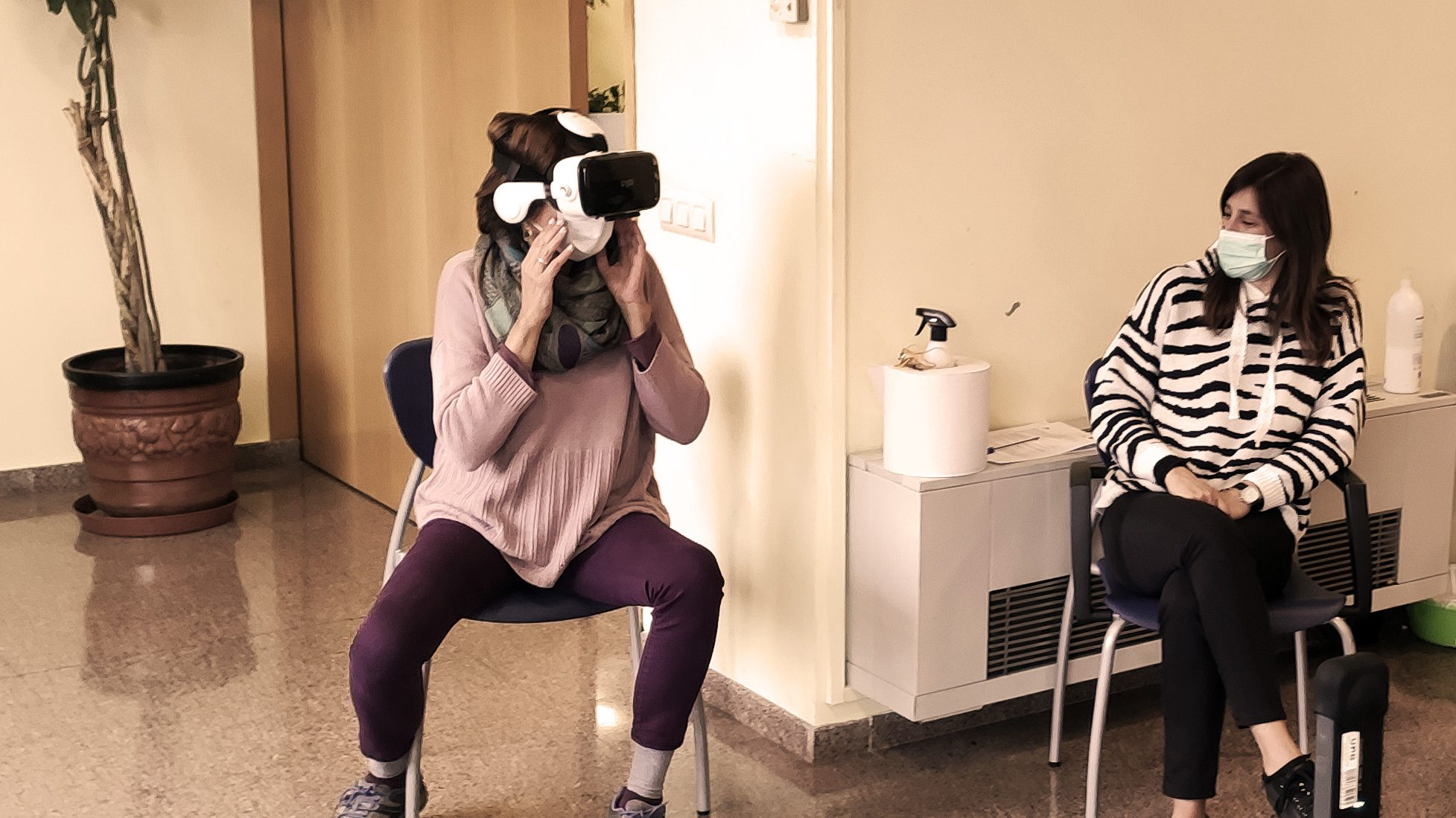 Image shows two female participants that test a Virtual Reality head-mounted display for the first time in their life. One participant observes the other, how she handles the VR experience.