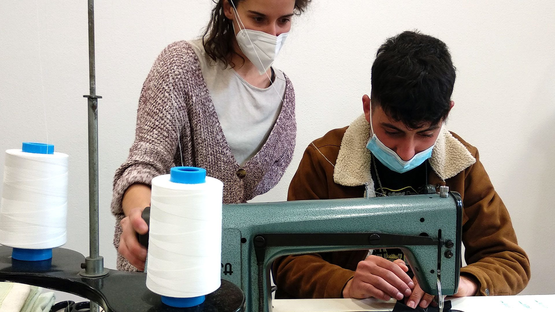 The image shows how the female instructor Carlota Rodriguez is guiding a participant of the Faberlull Residence with the sewing machine