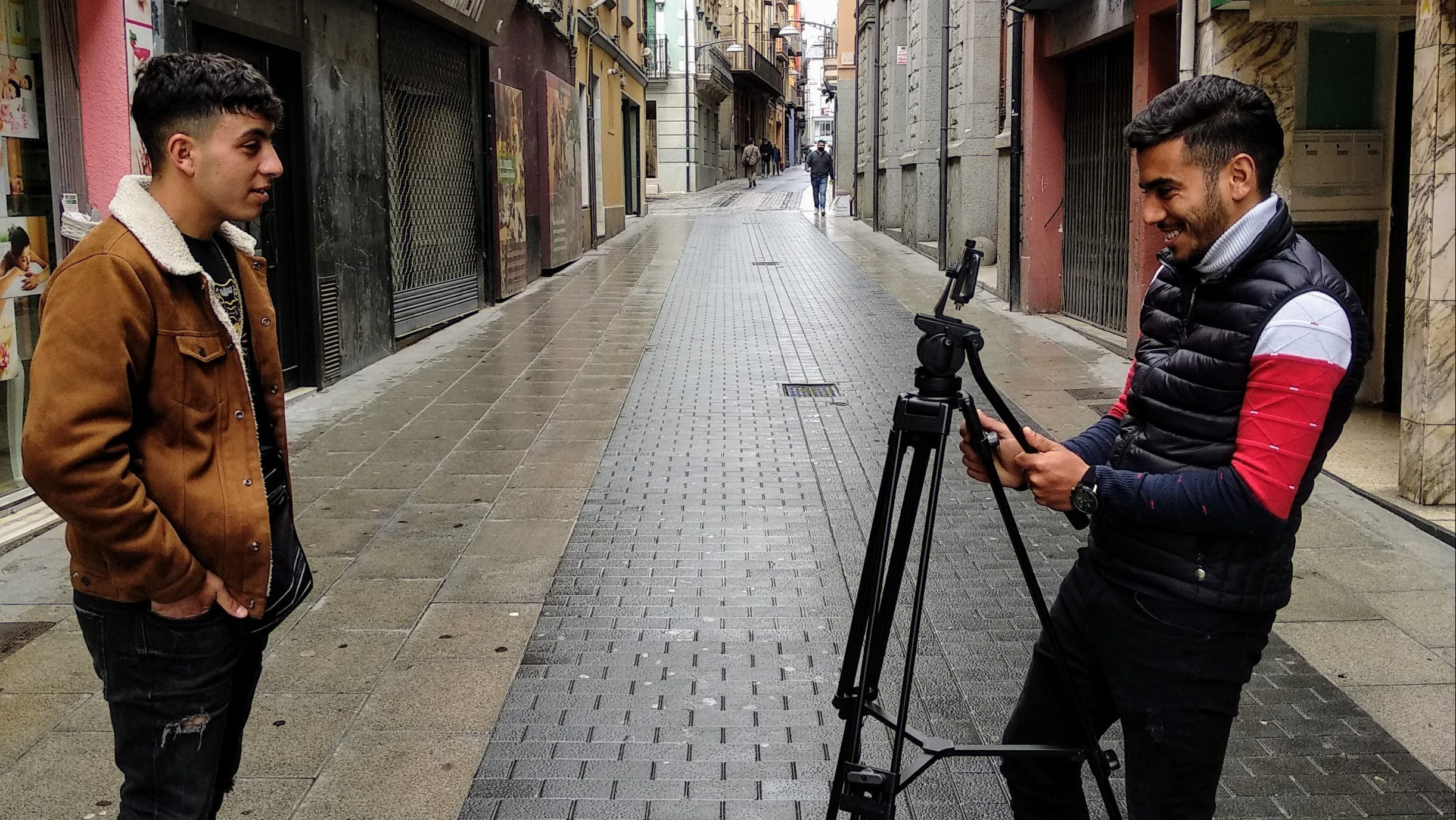 The image shows two young men in the streets of Olot, Spain. They are equipped with filing gear. One man is filming the other.